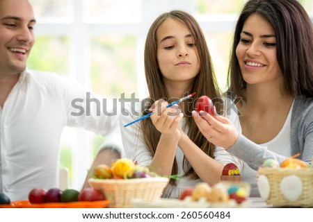 beautiful young daughter painting Easter eggs while parent looking her  - stock photo