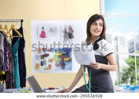 Beautiful young designer using laptop in studio - stock photo