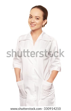 Beautiful young doctor wearing doctor's overall and looking at camera against of white background - stock photo