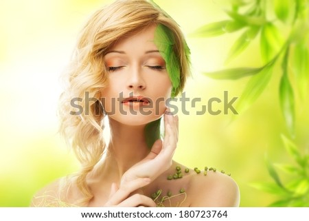 Beautiful young dreaming woman in conceptual spring costume touching her face