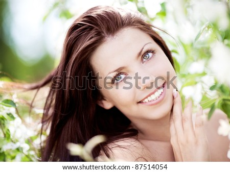 beautiful young dreamy woman looking up, standing  near the apple tree on a warm summer day