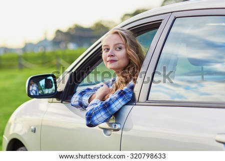 Beautiful young driver looking out of the car window