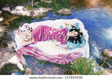 beautiful young elegant woman lie on linen floating on  clear mountain river - stock photo