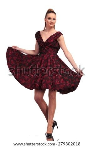 Beautiful young elegant woman smiling to the camera while she is playing with her dress. - stock photo