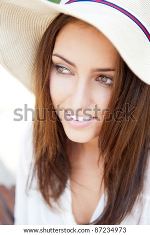 Beautiful young elegant woman wearing hat outdoor at park she is relaxed and daydreaming