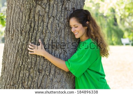 Beautiful young environmentalist embracing tree trunk in park - stock photo