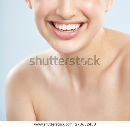 Beautiful young European woman with fresh smooth glowing skin. Beautiful white healthy teeth. - stock photo
