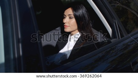 Beautiful young executive sitting in limousine - stock photo