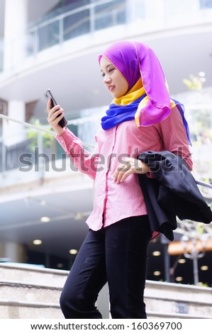 Beautiful young executive using tablet phone outdoor