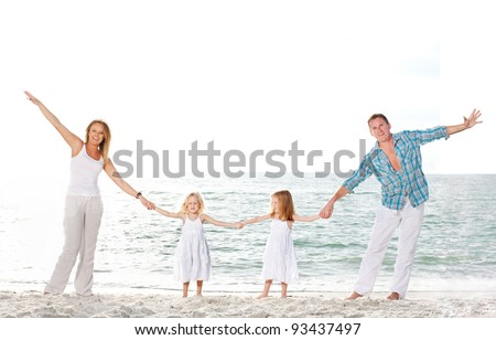 Beautiful young family enjoy sunny day at the beach. - stock photo
