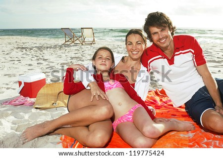Beautiful young family enjoying a day at the beach while relaxing on a large towel - stock photo