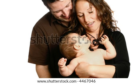 Beautiful young family having fun with their baby girl. Little girl carried by the mother and looking up and back to her dotting parents. - stock photo