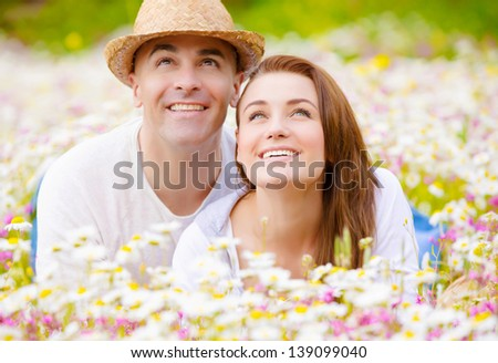 Beautiful young family laying down on wild camomile glade and looking up on sky, having fun in spring park, love concept
