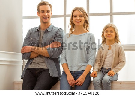 Beautiful young family looking in camera and smiling while sitting near the window at home - stock photo