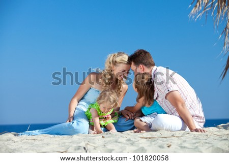 Beautiful young family lying and smiling on the beach - stock photo