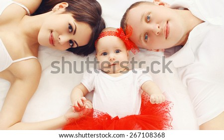 Beautiful young family lying together on the bed at home, parents and baby, top view - stock photo