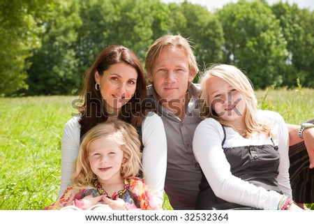 Beautiful young family outdoors in the field