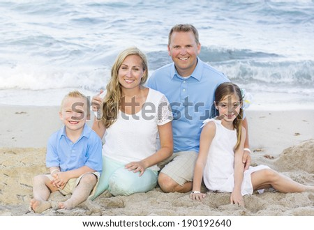 Beautiful young family Portrait at the beach - stock photo