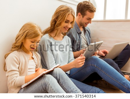Beautiful young family using tablets and smiling while sitting on the floor near the window at home - stock photo