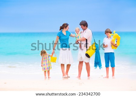 Beautiful young family with three children, happy boy, cute toddler girl and a little baby walking together on a tropical island beach during summer vacation - stock photo