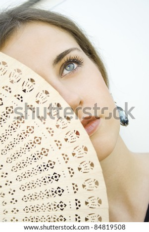 Beautiful young fashion girl with a wooden fan that covers half her face - stock photo