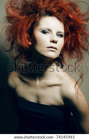 Beautiful young fashion model with curly red hair.