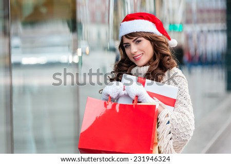Beautiful young fashion woman holding shopping bags and and a gift box standing near shop window with christmas hat. Outdoors. - stock photo