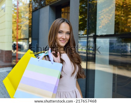 Beautiful young fashion woman holding shopping bags and standing near shop window - stock photo