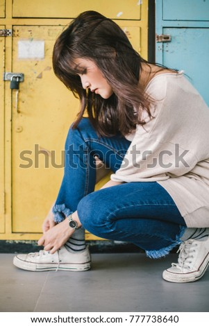 Beautiful young fashion woman model in front of locker. She is wearing a shoelace.