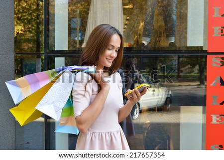 Beautiful young fashion woman with shopping bags near shop window calling smart phone - stock photo