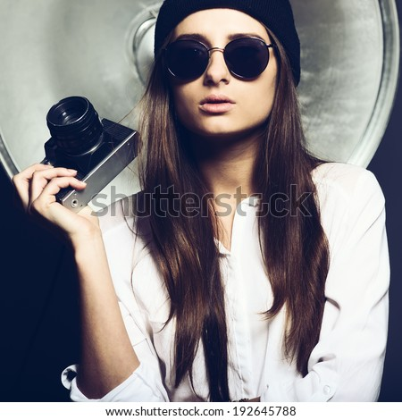 Beautiful young fashionable girl in a cap and glasses with a camera in the studio