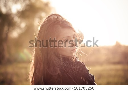 Beautiful young fashionable girl in the rays of spring sun