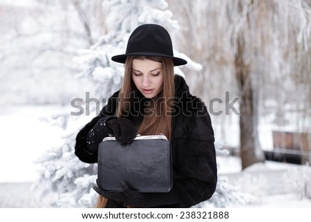 Beautiful young fashionable trendy girl in luxury fur coat stylish hat with black leather bag. Fashion portrait outdoor, winter - stock photo