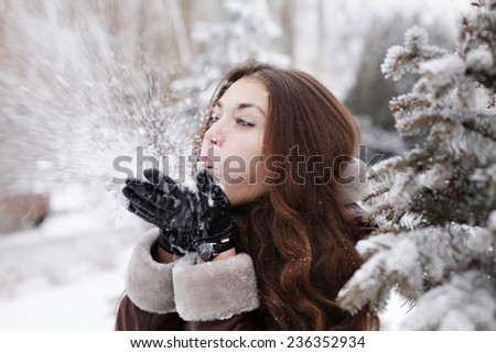 Beautiful young fashionable woman in black hat playing with snow outdoor winter lifestyle happiness emotions nature on background. People, holidays, fashion and magic concept - stock photo