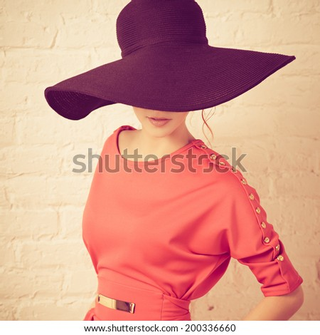 Beautiful young fashionable woman posing in red dress and black hat. Vogue style. Photo with instagram style filters - stock photo