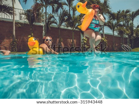 Beautiful young fat woman is jumping into the summer water pool with yellow duck   lifebuoy - stock photo
