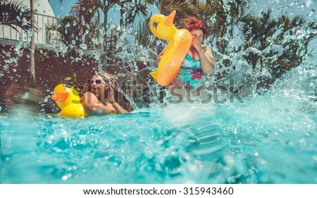 Beautiful young fat woman is jumping splash into the summer water pool with yellow duck lifebuoy