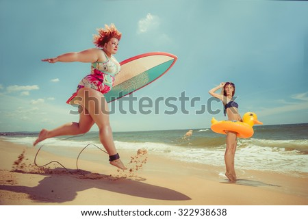Beautiful young fat woman is runing to the summer sea with the surfboard  - stock photo