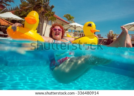 Beautiful young fat woman relaxing in the pool with yellow duck lifebuoy - stock photo