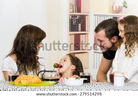 Beautiful young father mom fruit to small daughter - stock photo