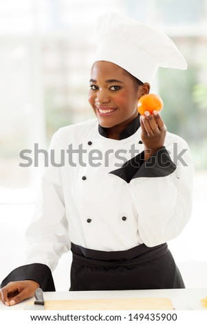 beautiful young female african chet holding fresh tomato - stock photo