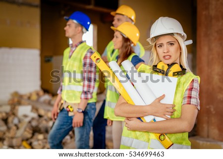 Beautiful young female construction architects at a construction site. She is holding plans and looking at camera.