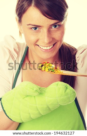 Beautiful young female cook tasting some food