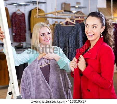 Beautiful young female customers selecting coats and jackets at the store. Focus on the right woman