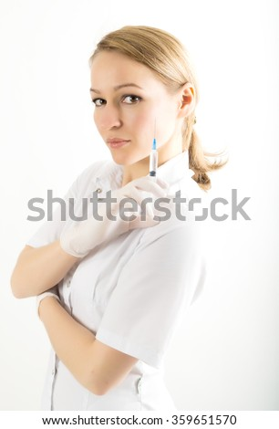 beautiful young female doctor in medical gown and rubber gloves holding a syringe. nurse - stock photo