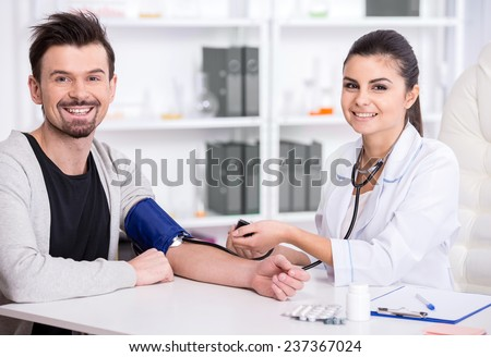 Beautiful young female doctor is checking the blood pressure of the patient. - stock photo