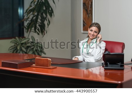 Beautiful Young Female Doctor Woman In office Talking On Cell Phone - Healthcare Worker Working Online