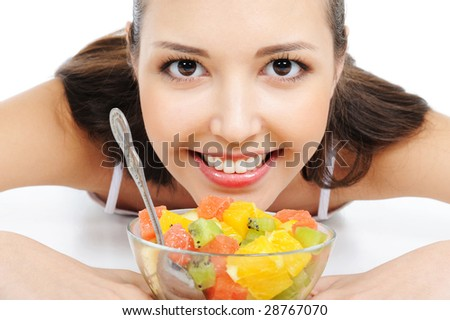 beautiful young female face under the bowl with fruit salad