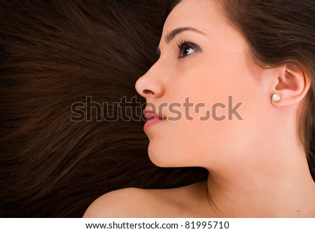 Beautiful young female face with long beauty hair as background - stock photo