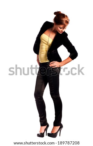 Beautiful young female fashion Model dressed in black fitting trousers, black jacket and yellow top on high heels standing and looking down - stock photo